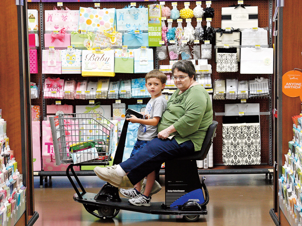 A woman riding an electric cart shops with a child at a Walmart Supercenter in Rogers, Arkansas June 6, 2013. The annual shareholders meeting for Walmart takes place on  June 7. REUTERS/Rick Wilking (UNITED STATES - Tags: BUSINESS) - RTX10E4B