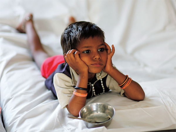 A malnourished child waits for food at the Nutritional Rehabilitation Centre in Sheopur district in the central Indian state of Madhya Pradesh April 6, 2010. India ranked 65th out of 84 countries in the Global Hunger Index of 2009, below countries including North Korea and Zimbabwe -- hindering India's ambitions to channel its demographic dividend to fuel its global economic ambitions. Picture taken April 6, 2010. To match feature INDIA-WELFARE/  REUTERS/Reinhard Krause (INDIA - Tags: BUSINESS FOOD HEALTH SOCIETY) - RTR2D108