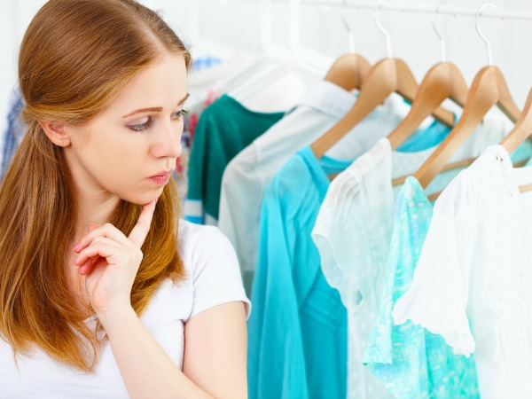 young woman chooses clothes in her wardrobe