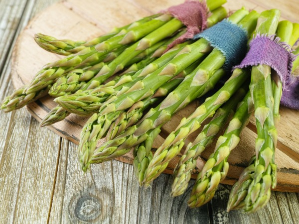 Bunch of fresh green asparagus on wooden background, rustic style