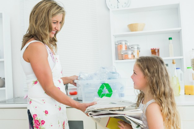Mother taking newspaper from daughte for recycling