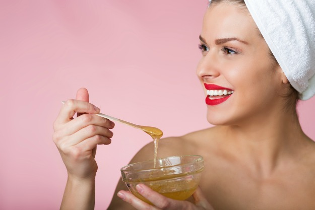 Woman holding sugar hair removing paste