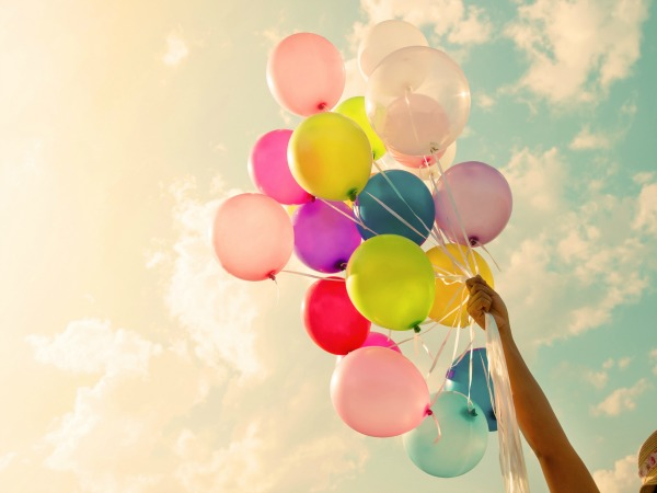 Girl hand holding colorful balloons. happy birthday party. vintage filter effect