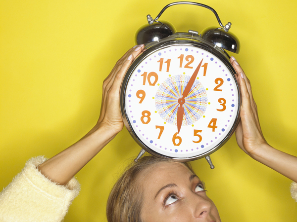 Woman holding clock over her head