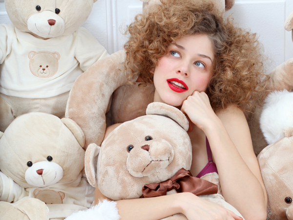 A young woman covered in teddy bears