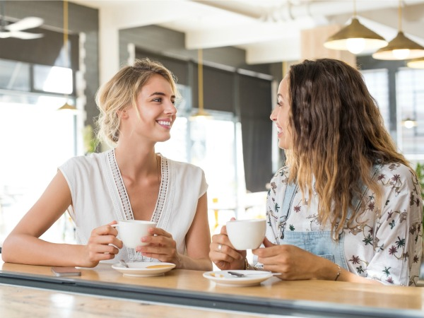 Two beautiful young women holding cup of coffee and talking to each other. Young blonde woman in conversation with her best friend while sipping a cup of capuccino. Friends meeting up for coffee after a long time.