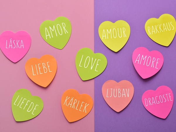 some heart-shaped sticky notes of different colors with the word love written in different languages, such as Spanish, Portuguese, Italian, French, Polish or Dutch, on a pink and violet background
