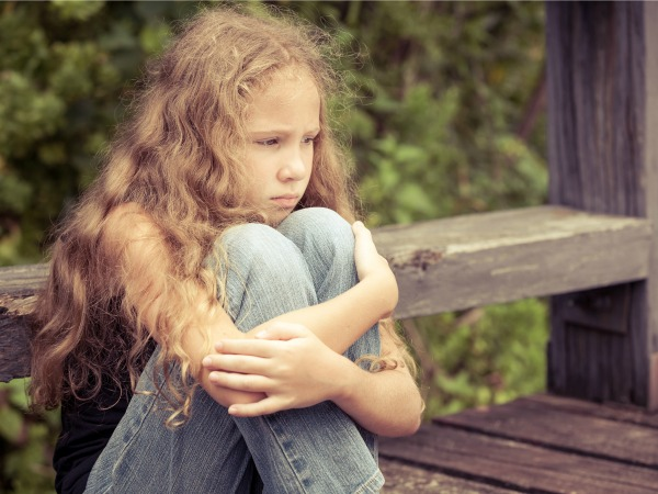 Portrait of sad blond teen girl sitting on the bridge at the day time