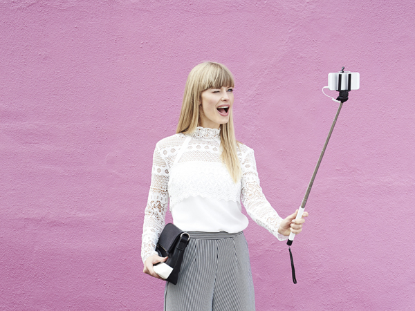 Young blond woman winking for selfie against pink wall