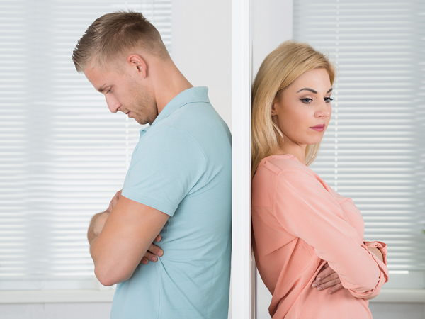 Side view of unhappy young couple standing back to back at home