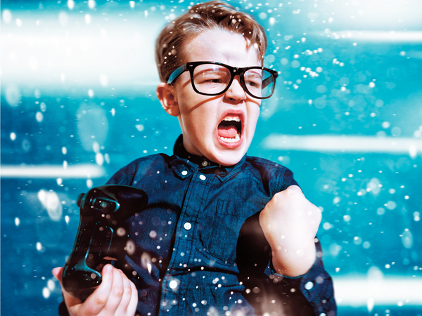 Boy holds a game controller in one hand and cheers. Sparks fly through the air. The boy wears glasses.