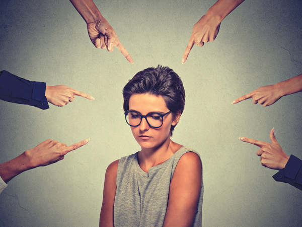 Concept of accusation guilty shy person girl. Sad embarrassed upset woman in glasses looking down many fingers pointing at her isolated grey wall background. Human face expression emotion feeling