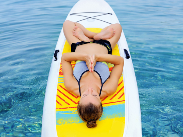 Young woman practicing laying padmassana yoga pose on sup board on water