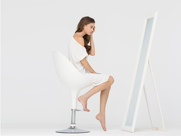 Woman sitting on a chair and looking at mirror