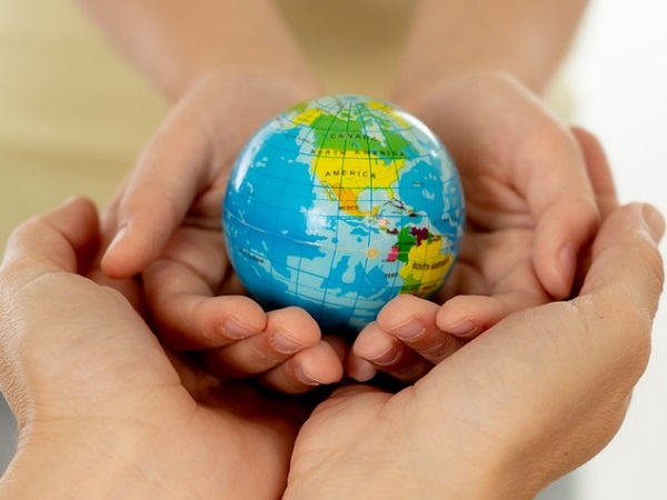 close up photo of mother and child holding hands with a world globe in their hands in better world idea protection and education concept (close up photo of mother and child holding hands with a world globe in their hands in better world idea protectio