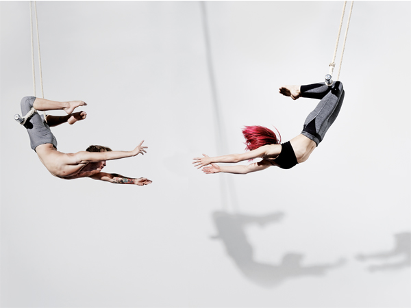 Circus artists in Trapeze, Photographed on white, with shadow projected on the wall