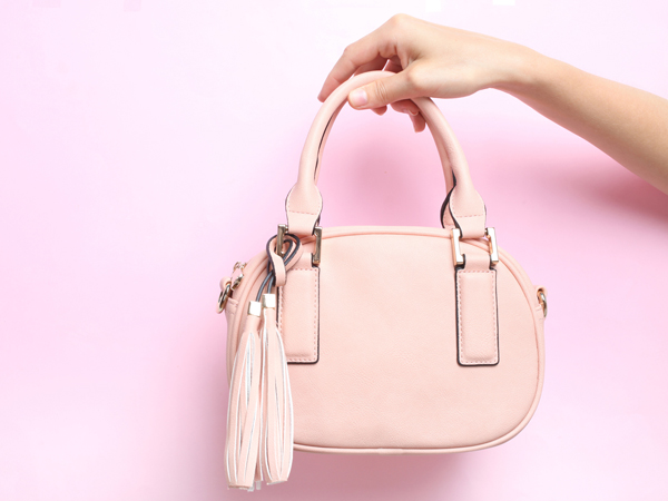 Female bag in hand on a pink background