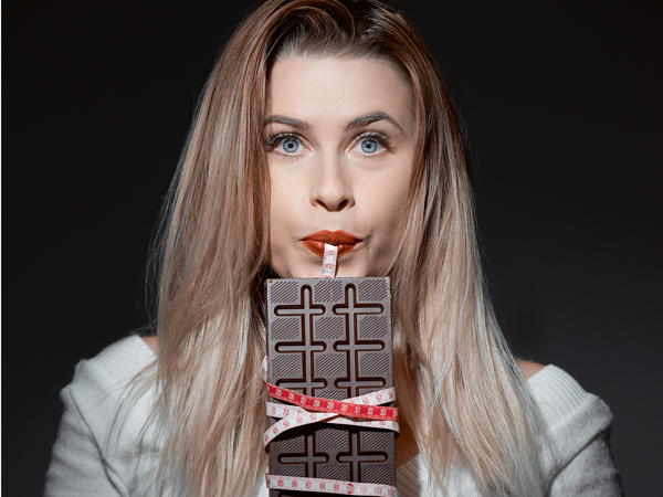 lifestyle shot of young woman inside studio shot holding chocolate with tape line surrounding it, dieting concept.