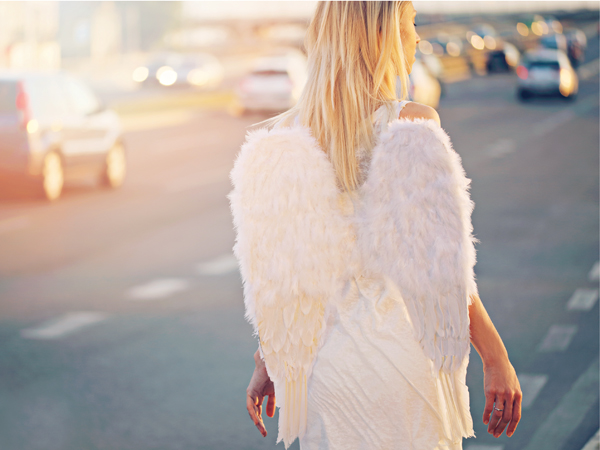 Young beautiful woman with angel wings walking near highway, freedom concept