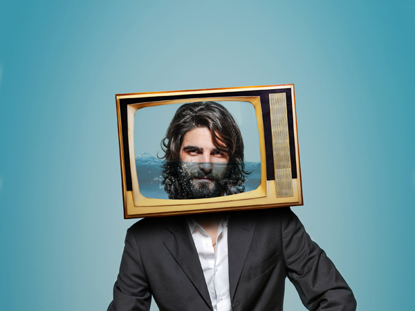 Man sitting with TV for head with face.Digital composite