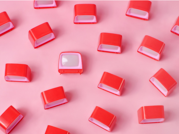 Random pattern of a group of red plastic toy televisions arranged on a pink background