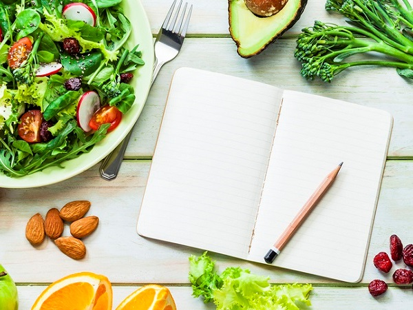 Healthy eating and dieting concepts: Top view of a fresh organic salad plate placed at the top left of the frame. A yellow tape measure is beside the salad plate and goes from top to bottom of an horizontal frame. A blank note pad with useful copy space for text and a pencil are at the right.  Fruits and vegetables like a green apple, cherry tomatoes, almonds, avocado, broccoli and lettuce are all around the notepad. Predominant color is green. High key DSRL studio photo taken with Canon EOS 5D Mk II and Canon EF 100mm f/2.8L Macro IS USM.