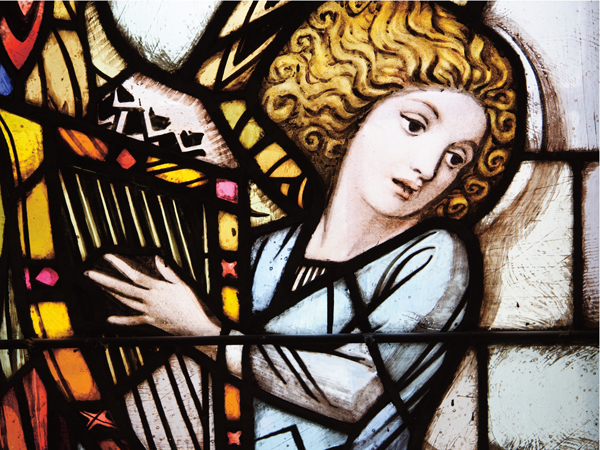 ancient stained glass angel playing a harp