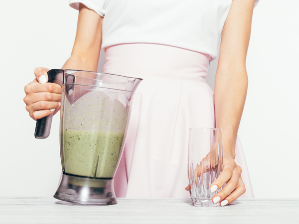 Slender young woman in a pink skirt pours a green smoothie from a banana and spinach into a glass
