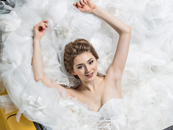 High angle view of young bride in wedding dress sitting in convertible