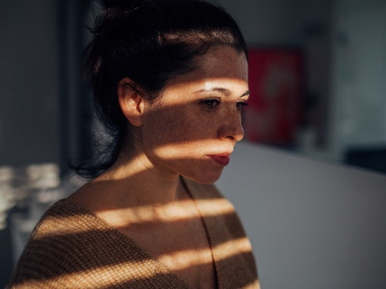 Portrait of a sad young woman in her apartment, with a sun on her face, that is breaking through the window blinds // wide photo dimensions