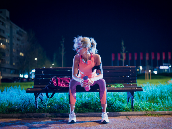 Young sports woman resting after training outdoors