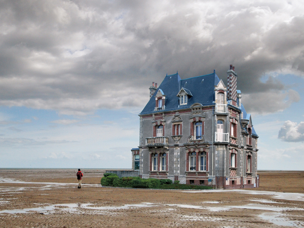 Ouistreham, France - June 27, 2014: the cast of Normandy in summer; a house standing on the beach. A person is passing by.
