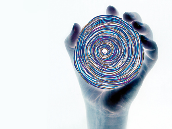 Person holding coil of colored wires, close-up (digital enhancement)