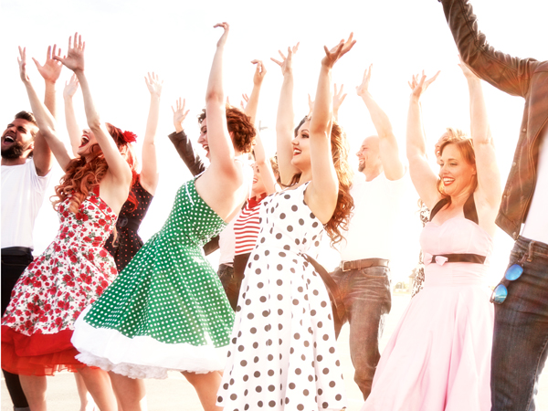 "A crowd of Fifties party dancer dressed up girls and cool greaser guys all have their arms and hands up waving in the air - rocking out dancing at the sunset sun flare high school graduation dance with all their friends. Fifties image from June 2015 Utah ""War and Peace"" photo shoot."
