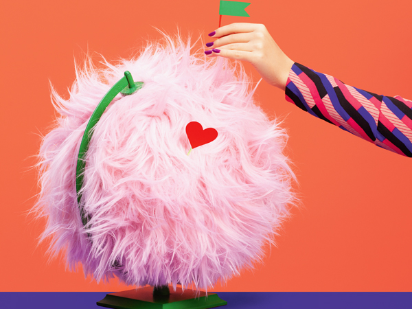 Image of pink plush covered globe with hand pinning flag to illustrate the concept of home.