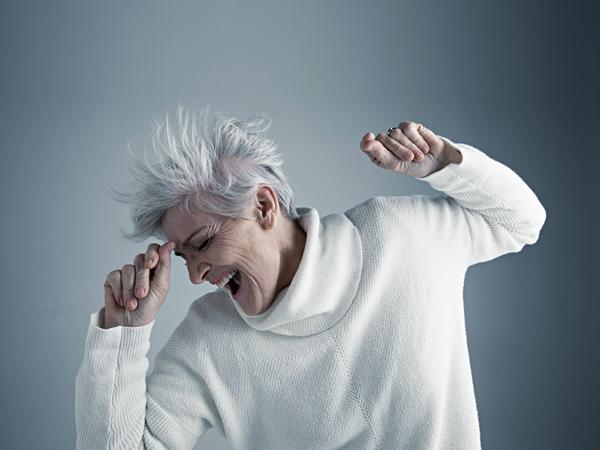 Portrait playful Caucasian senior woman with short gray hair dancing