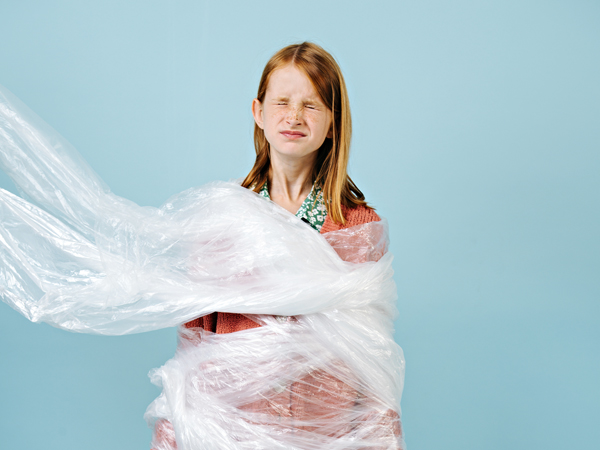 Unhappy trapped teenage redhead girl is wrapped in plastic in protest of waste crisis. She closed her eyes. No more. Recycling and ecology.