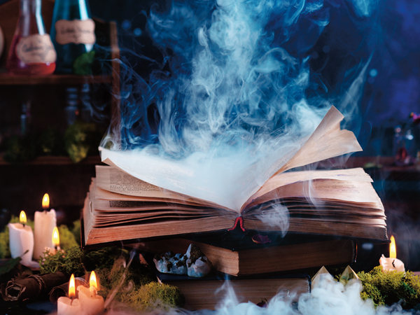 Magical spell book with mysterious smoke. Witch workplace with potions and herbs. Open book on a dark background with copy space