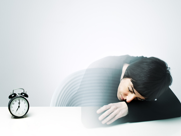 Young woman having a nap on a table. She's half transparent because she's at half way from her dreams. The clock is at waking up time.