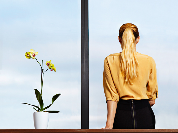Businesswoman sitting on desk looking out window