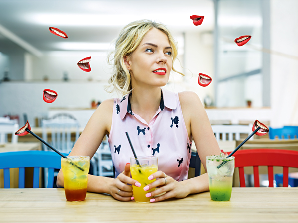 Beautiful blonde sitting at a table with three different cocktails in beautiful glasses with straws surrounded by abstract lips that give it a different life advice. Creative photo collage.