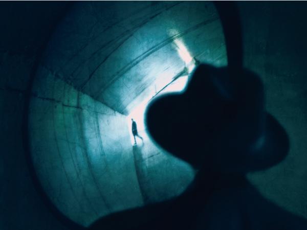 Man Looks in Mirror in Tunnel