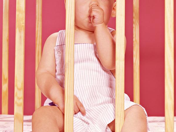 UNITED STATES - CIRCA 1950s:  Baby in playpen, sucking thumb.