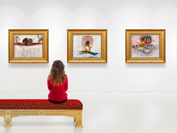 In a exhibition centre, lonely young woman wears red jacket, visits an art exhibition and watches artist's collection on the wall. Lightened white wall contains four gilded frames and Artist's paintings.